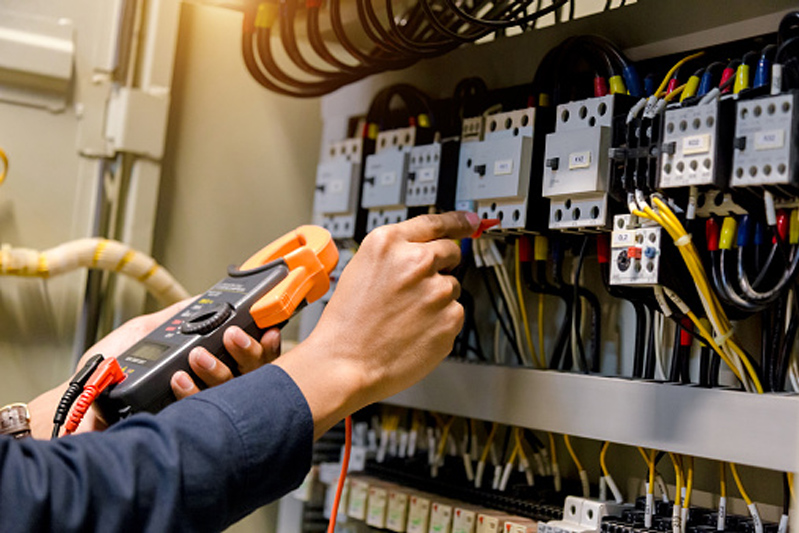 Electrician engineer measuring voltage and current of power electric line in electrical cabinet control