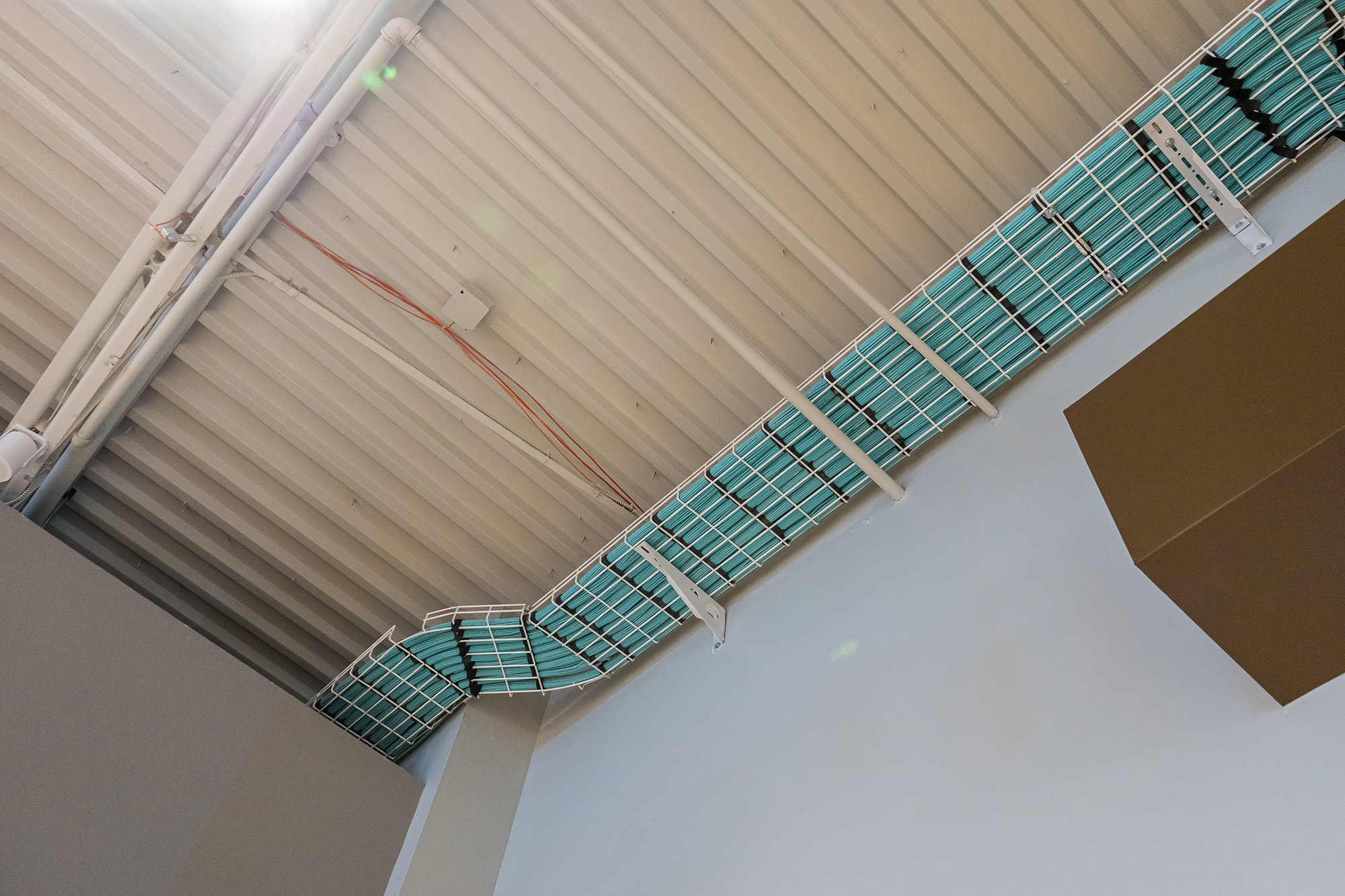 Blue cables secured to the ceiling of a room.