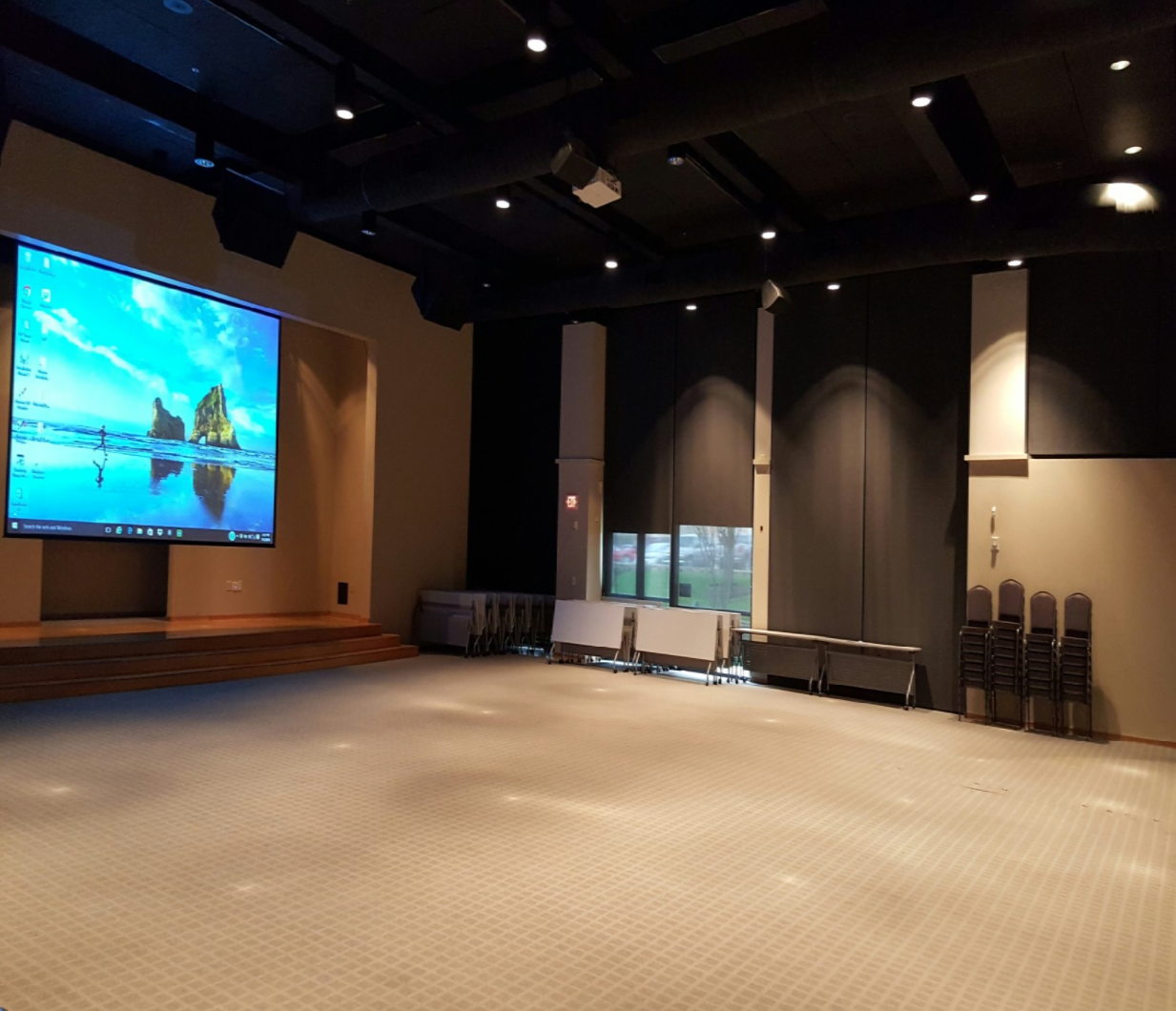 Meeting room with no furniture and a desktop screen projected on a projector screen