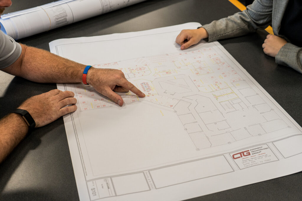 Two people analyzing a CTG blueprint at a table