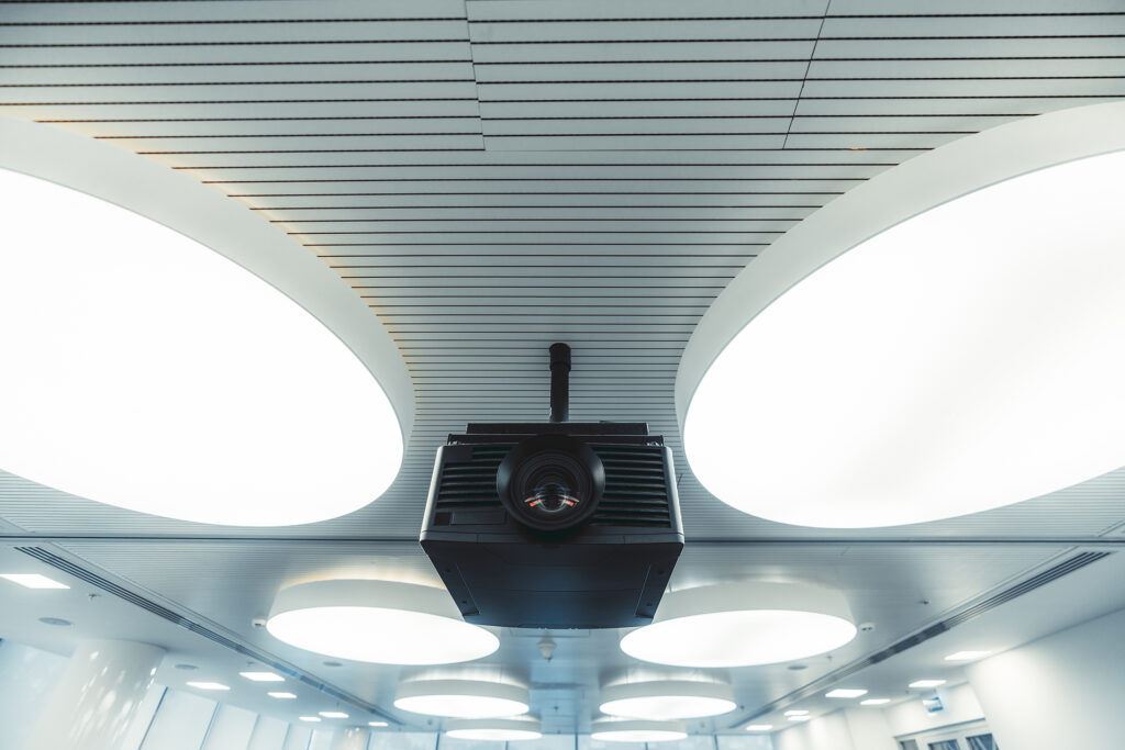 Wide-angle view of a black modern projector with a plastic case and a huge lens with aberrations on it, mounted to the ceiling with multiple large round ceiling lamps lighting a modern conference room