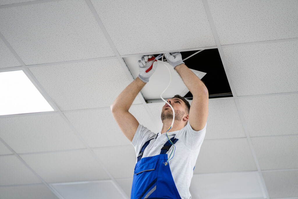 Electrician on a stepladder installs lighting into the ceiling