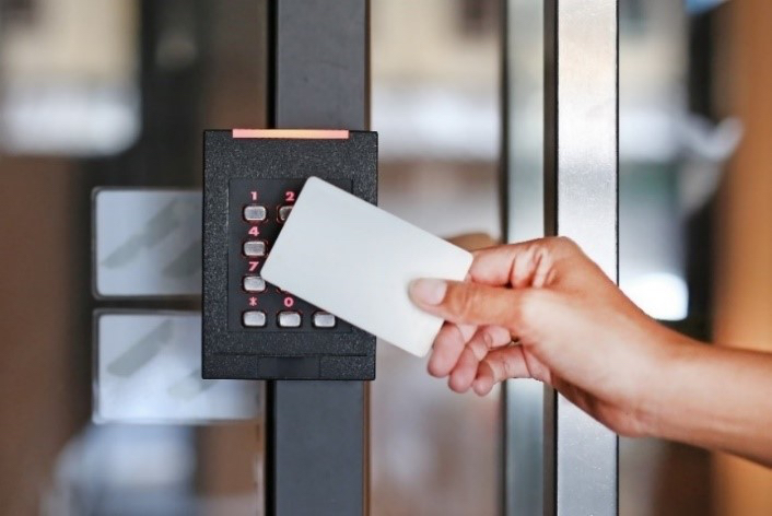 Person swiping a white card on a black security keypad