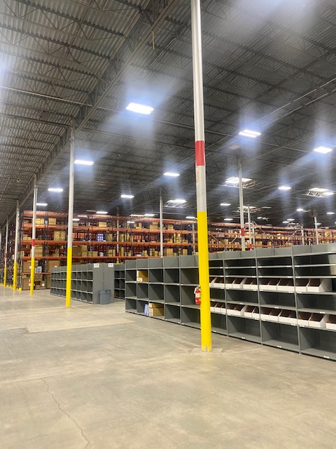 Overview of warehouse including floor to ceiling yellow poles, large cubbies and shelves filled with boxes