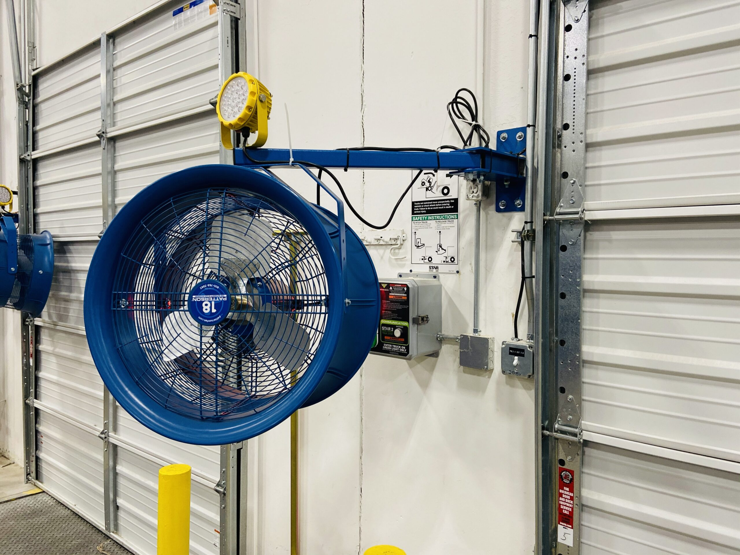 Blue fan attached to the wall by a garage door